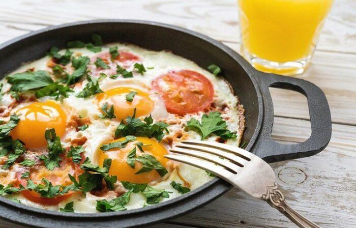 Зажарить до готовности, не перемешивая, перед подачей присыпать нарезанной свежей зеленью. Яйца с помидорами и зеленью