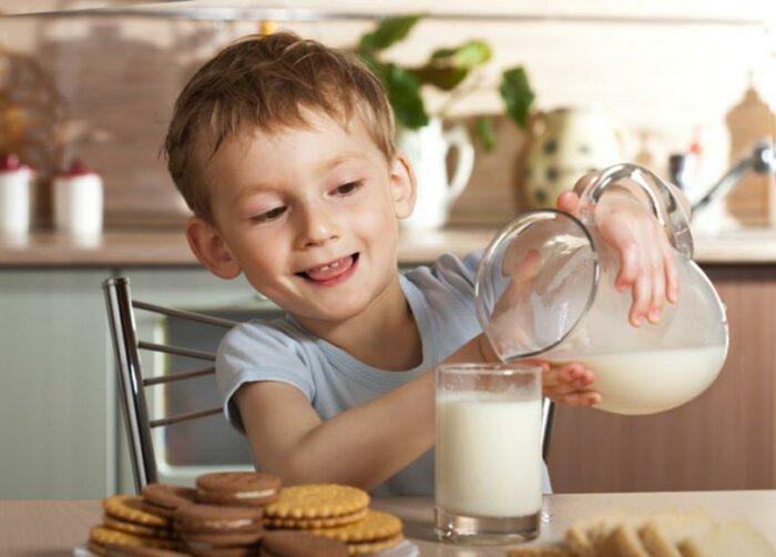 ребенок наливает молоко